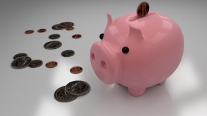 Coins going into a pink piggy bank